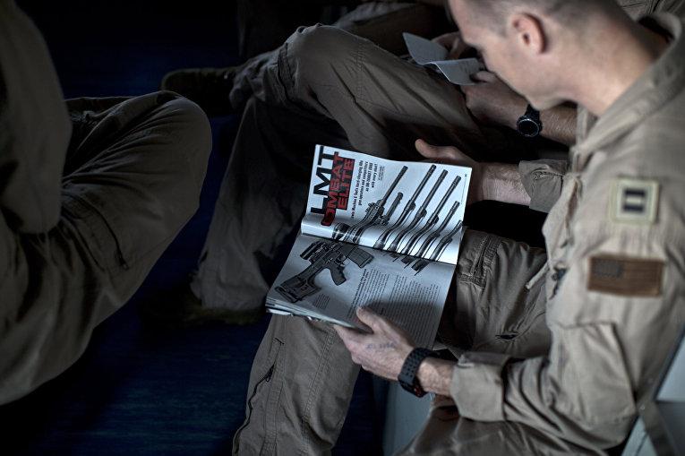 Военный летчик читает журнал об оружии на борту авианосца «Теодор Рузвельт»