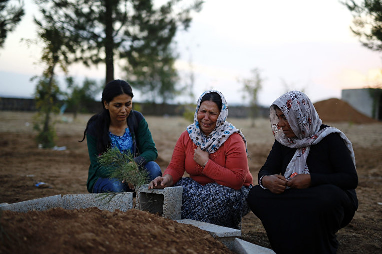 Женщины у могил курдских ополченцев, воевавших с боевиками Исламского государства в Кобани
