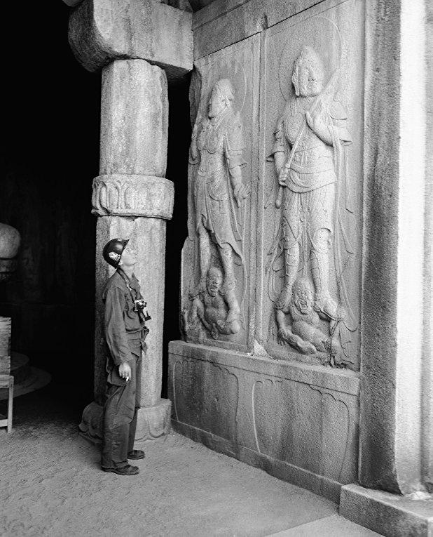 Американский солдат рассматривает барельефы в храме, Корейская война 1950-1953 годов