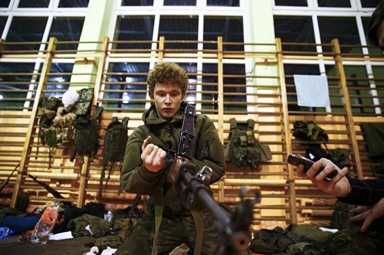 Дамиан Трынкевич собирает автомат в перерыве на занятии по оказанию медицинской помощи, организованном вооруженным формированием Obrona Narodowa