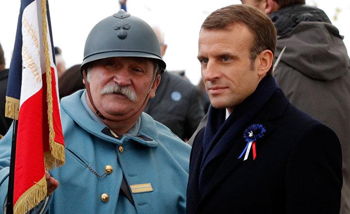 Президент Франции Эммануэль Макрон и реконструктор, одетый как солдат французской армии времен Первой мировой войны, во время памятной церемонии в коммуне Моранж. 6 ноября 2018