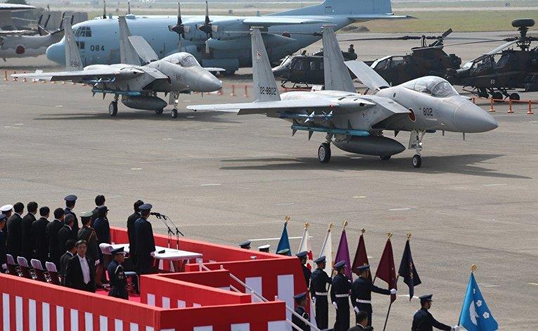 Премьер-министр Японии Синдзо Абэ осматривает истребитель F-15J на авиабазе Хякури