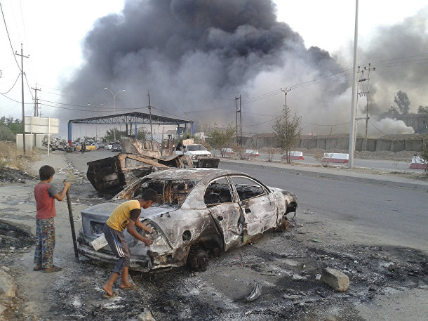 Дети у сгоревшей машины во время столкновений между иракскими войсками и организацией «Исламское государство Ирака и Шама» городе Мосул