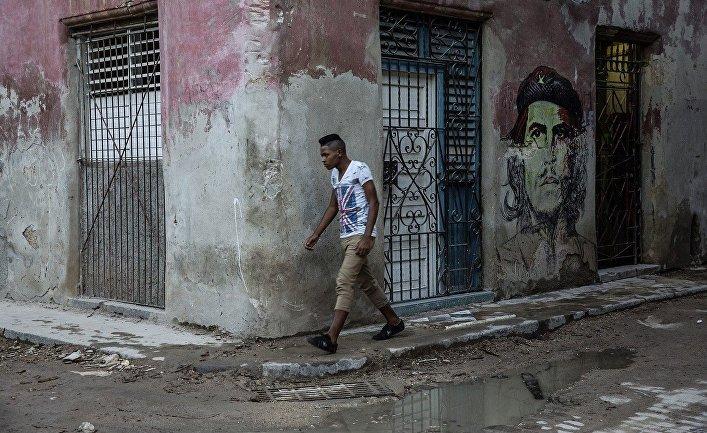 Юноша проходит мимо граффити с изображением Че Гевары