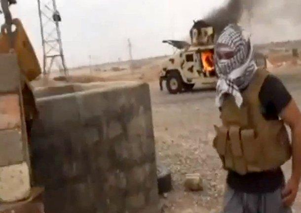 Боевик «Исламского государства Ирака и Шама» у горящего «Хаммера» иракской армии