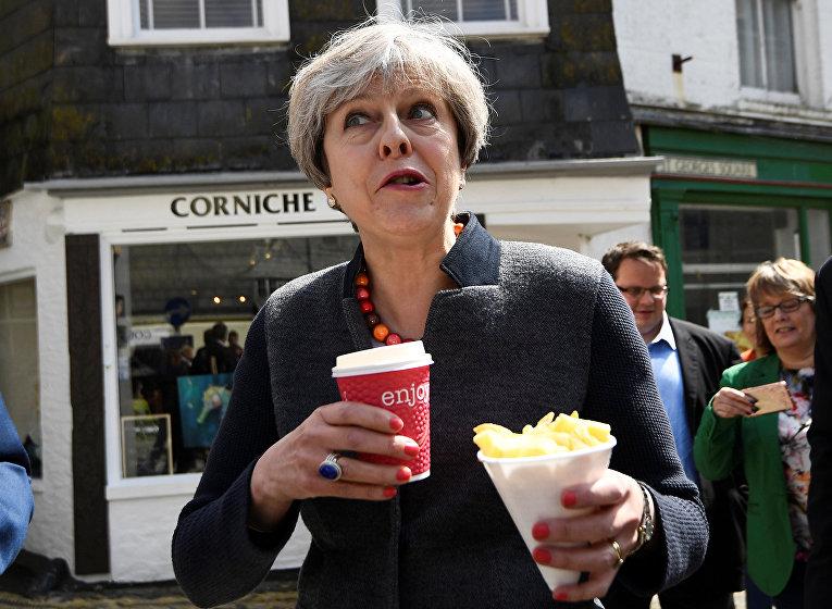 Премьер-министр Великобритании Тереза Мэй перекусывает во время встречи с жителями Мевагисси