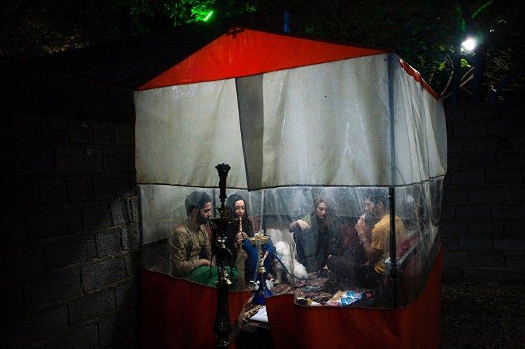 Молодые люди курят кальян в Тегеране