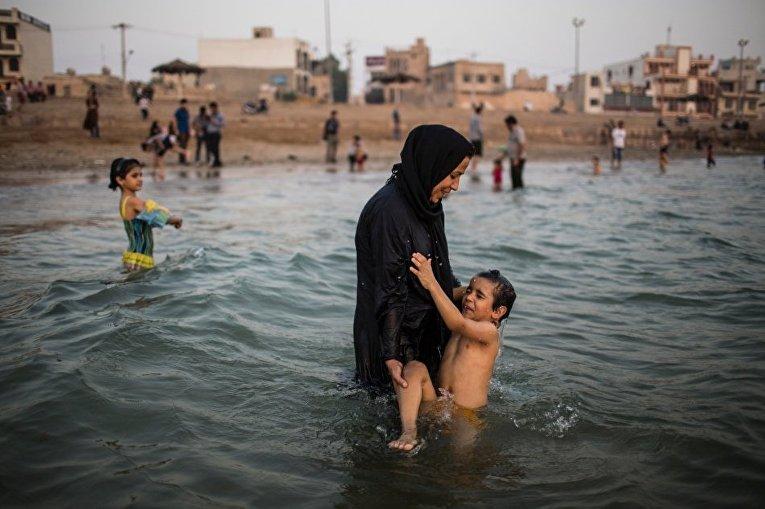 Женщина купает ребенка в Персидском заливе в городе Бушер
