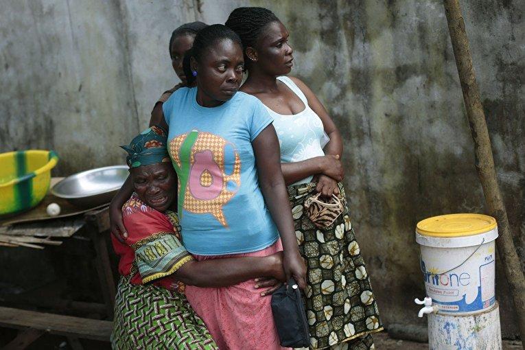 Женщина оплакивает свою дочь, умершую от лихорадки Эбола