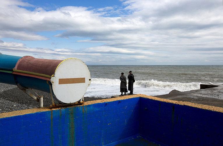 Люди стоят на берегу Черного моря в Алуште
