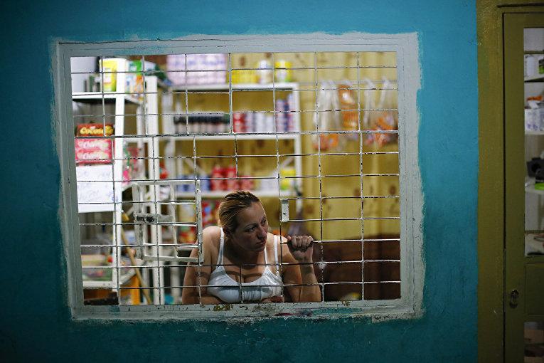 Женщина выглядывает из окна своего магазина в коридоре небоскреба «Башня Давида» в Каракасе