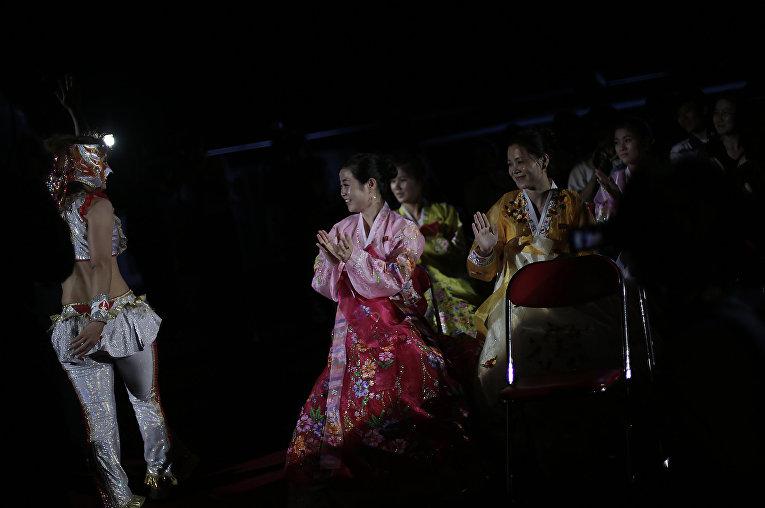 Женщины в национальных костюмах аплодируют рестлеру на шоу в Пхеньяне
