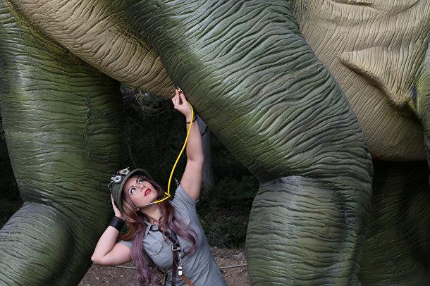 Косплеер позирует с моделью динозавра в натуральную величину на выставке в ботаническом саду в Крыму