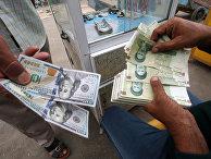 Иранские риалы и доллары США в пункте обмена валюты в Басре, Ирак