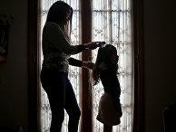 Моника Флорес расчесывает волосы ребенку-трансгендеру у себя дома в Сантьяго