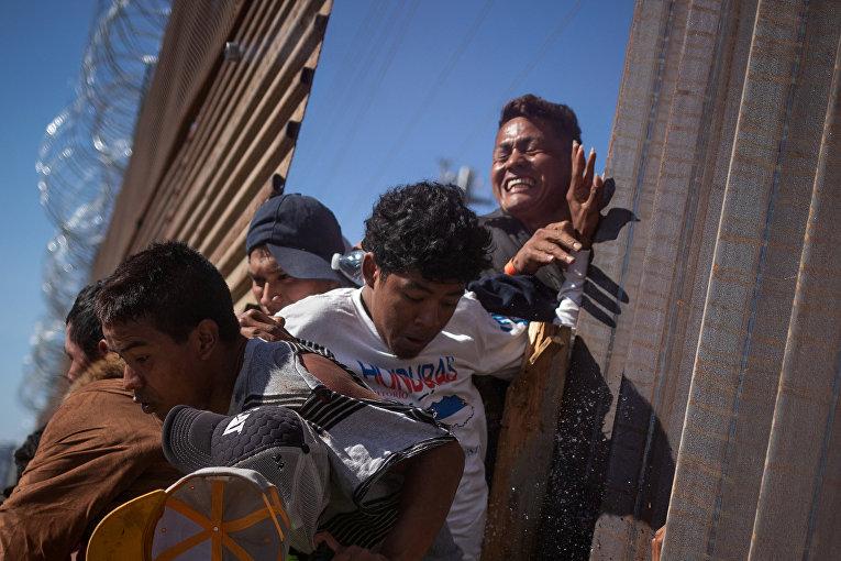 Мигранты пробираются через забор на границе, возвращаясь в Мексику после того, как полицейские применили слезоточивый газ