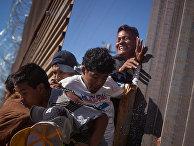 Мигранты пробираются через забор на границе, возвращаясь в Мексику после применения сотрудниками полиции слезоточивого газа в Тихуане