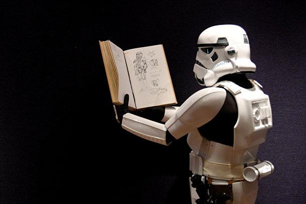 Человек, одетый в костюм штурмовика показывает книгу с иллюстрациями к костюмам «Звездных войн»
