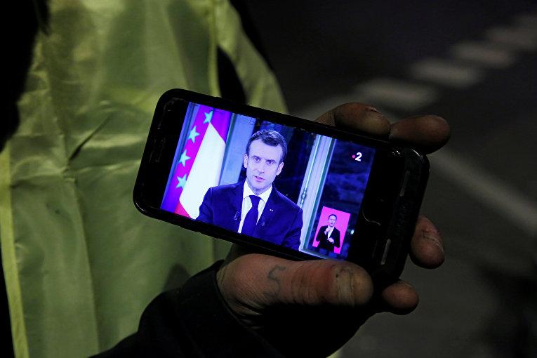 Протестующие смотрят обращением к нации президента Франции Эммануэля Макрона
