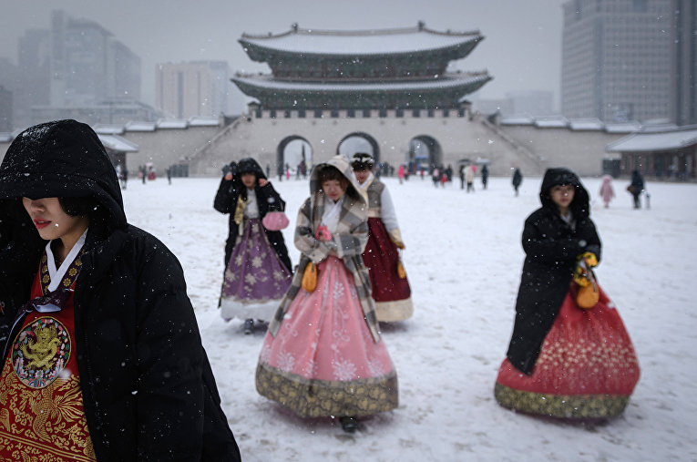 Посетители, одетые в традиционные платья ханбок во дворце Кенбоккун в Сеуле
