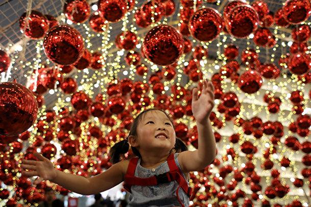 Девочка смотрит на рождественские украшения в торговом центре «Эмпориум»