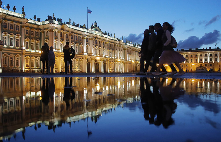 Люди гуляют на Дворцовой площади в Санкт-Петербурге