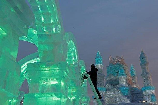 Скульптор по льду подготавливает один из экспонатов на фестивале льда