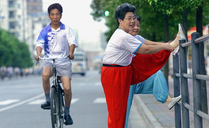 Жители Шанхая разминаются перед утренней зарядкой на улице