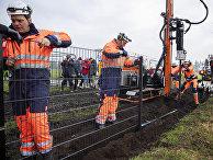 Рабочие установили забор на границе между Данией и Германией в Падборге, чтобы предотвратить пересечение границы дикими кабанами