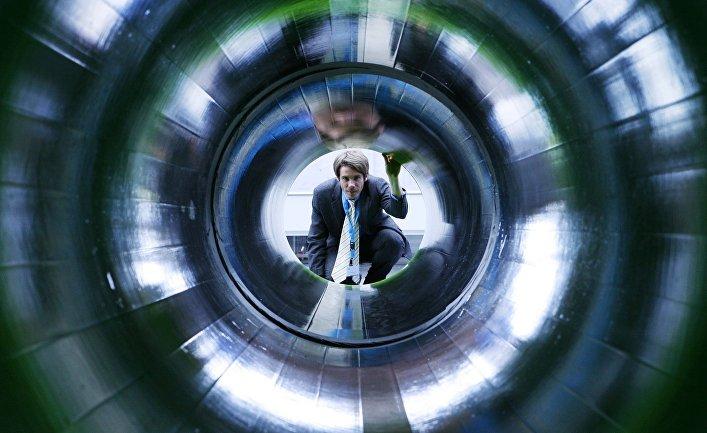 Мужчина заглядывает втрубу, представляющую газопровод «Северный поток», напромышленной выставке вГанновере