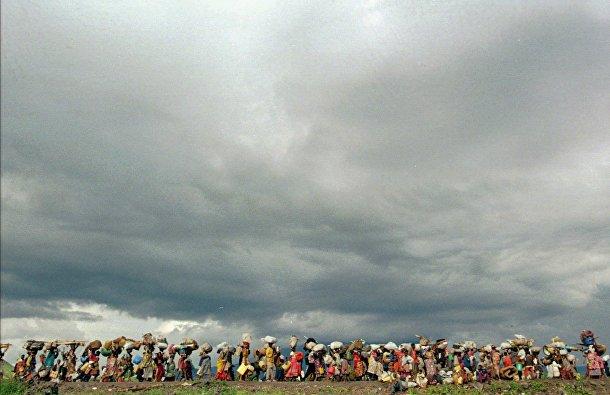 Беженцы выходят из лагеря беженцев Мугунга