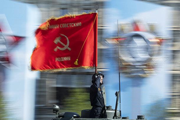 Солдат с флагом времен Великой Отечественной войны во время генеральной репетиции парада