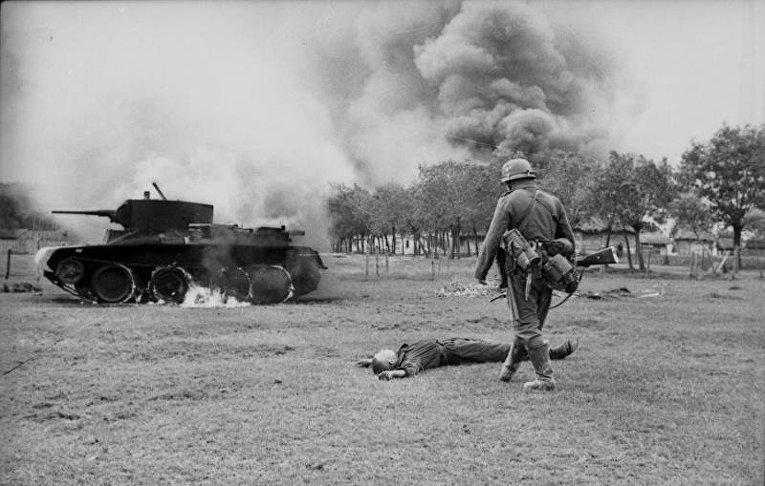 Немецкий пехотинец возле горящего советского танка БТ-5