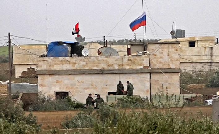 Российский флаг над зданием в районе Аримах к западу от Манбиджа недалеко от турецкой границы