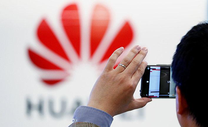 Мужчина фотографирует логотип Huawei в Европейском центре кибербезопасности Huawei в Брюсселе