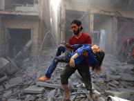 Мужчина спасает девочку из развалин после авианалета в Идлибе, Сирия