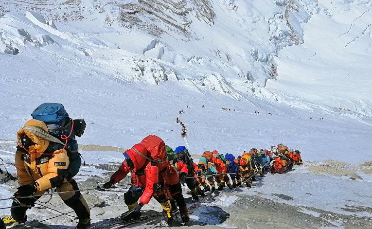 Цепочка альпинистов идет по тропе к вершине Эвереста