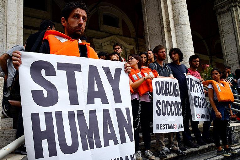 Участники демонстрации у министерства транспорта в знак протеста против политики итальянского правительства в отношении мигрантов в Риме