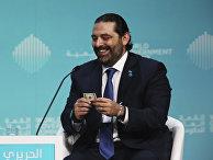 Премьер-министр Ливана Саад Харири со стодолларовой банкнотой