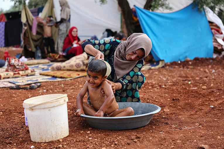 Женщина моет ребенка в тазу в лагере для беженцев неподалеку от Идлиба, Сирия