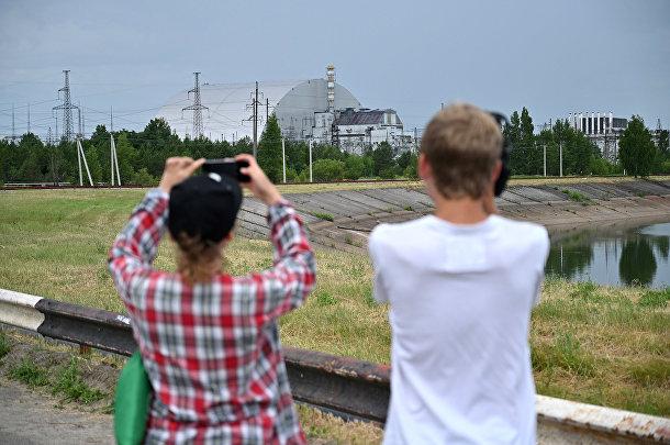 Люди фотографируют Чернобыльскую АЭС во время экскурсии