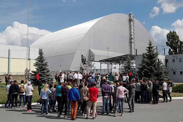 Туристы у нового безопасного саркофага над разрушенным в результате аварии 4-м энергоблоком Чернобыльской АЭС