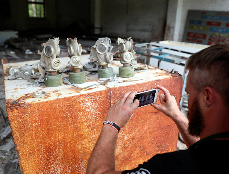 Турист фотографирует противогазы на бывшей базе советской армии возле Чернобыльской АЭС