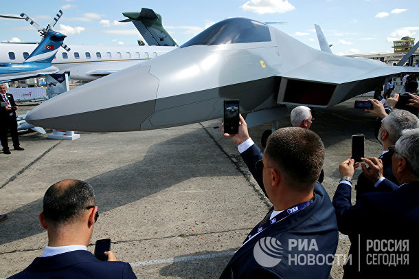 Посетители выставки фотографируют макет турецкого истребителя Turkish Aerospace
