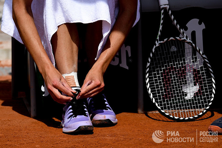 Теннисистка завязывает шнурки на кроссовках перед матчем