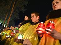 Украинцы держат свечи перед памятником чернобыльцам в Славутиче, Украина