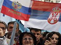 Сторонники премьер-министра Сербии Воислава Коштуницы держат российский и сербский флаг во время предвыборного митинга в Белграде