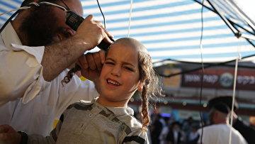 Еврей-хасид стрижет ребенка в честь наступающего Нового года Рош ха-Шана