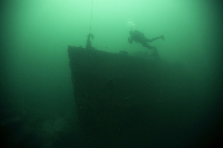 Дайвер осматривает остов затонувшего судна