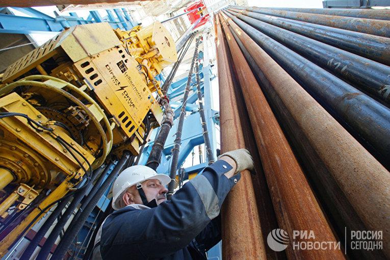 Бурильщик работает с пакетом буровых труб на берегу Балтийского моря